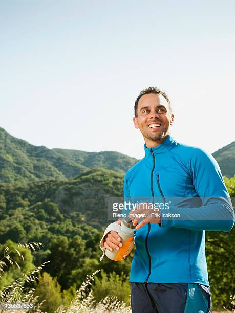 Athletic mixed race man drinking water outdoors