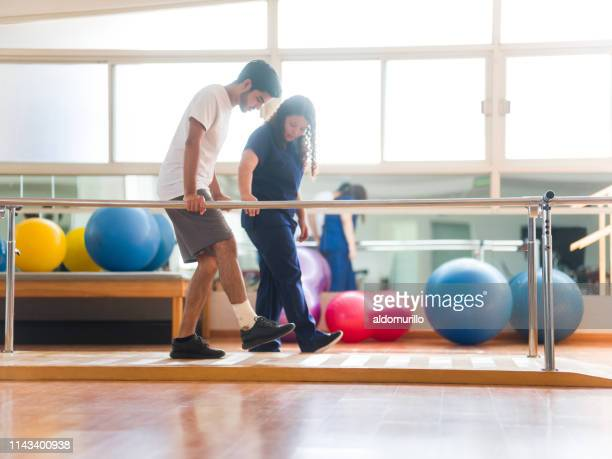 athletic patient walking in parallel bars - physical therapy stock pictures, royalty-free photos & images