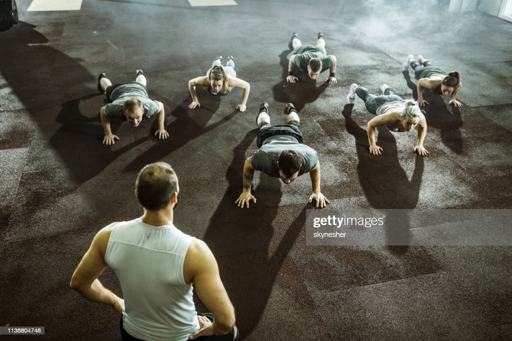 Athletic people doing push-ups on sports training with their coach. : Stock Photo