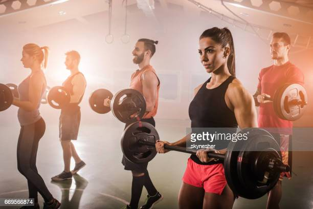 athletic people doing strength exercises with barbells in a gym. - circuit training stock photos and pictures