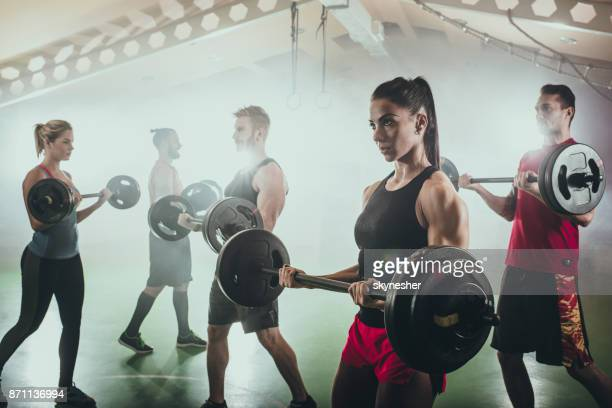 Athletic people doing strength exercises with barbells in a gym.