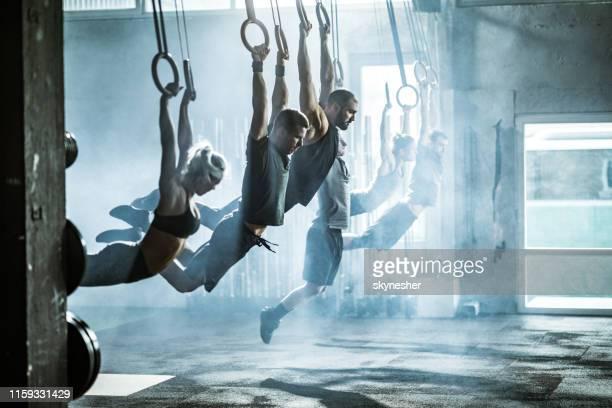 sportliche menschen mit krafttraining auf gymnastikringen in einer turnhalle. - frauen ringen stock-fotos und bilder