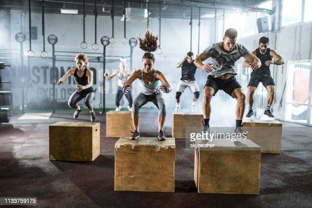 athletic people jumping on crates during cross training in a health club - effort stock pictures, royalty-free photos & images