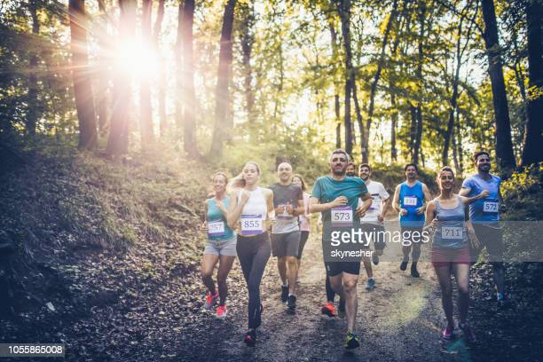 athletic people running a marathon through the forest. - half_marathon stock pictures, royalty-free photos & images