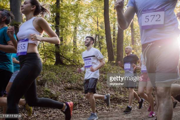 Athletic people taking a part in marathon race through the forest.