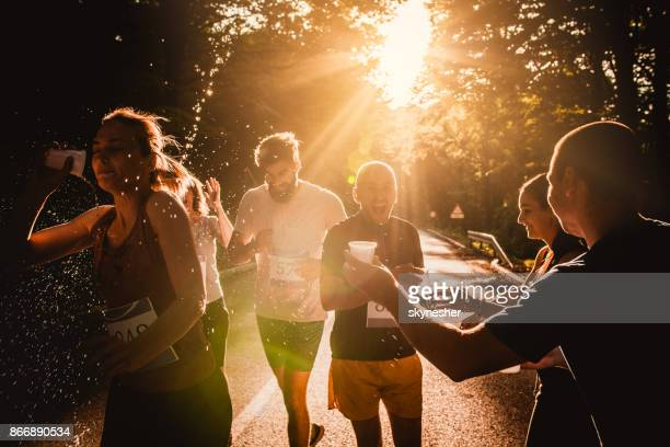 Athletic people taking fresh water from volunteers during marathon race at sunset.