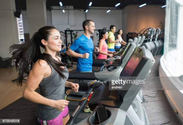 athletic people working out at the gym - treadmill stock pictures, royalty-free photos & images