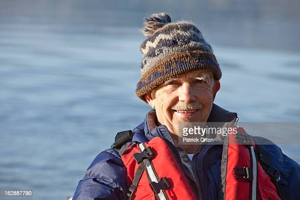 A athletic retired man smiling at the camera while kayaking on a lake in Idaho.