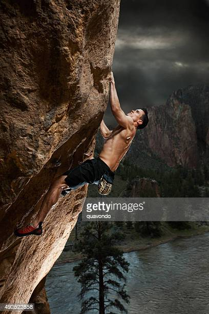 Athletic Rock Climber Hanging Off a Cliff
