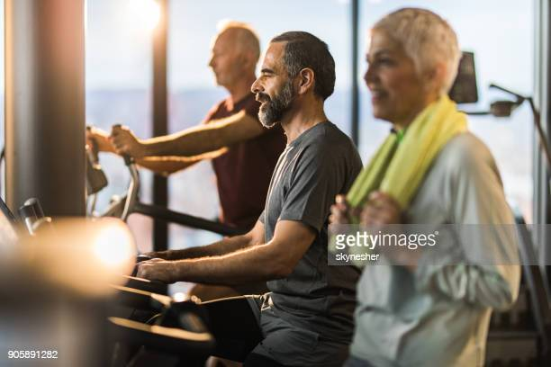 Athletic senior people cycling on exercise bikes in a health club.