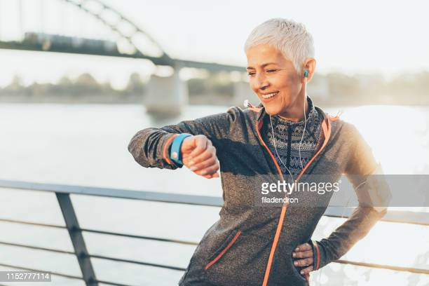athletic senior woman using smart watch - só uma mulher idosa imagens e fotografias de stock