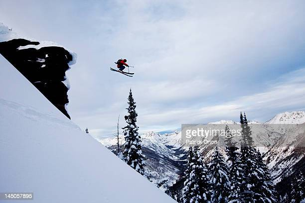 A athletic skier jumping off a cliff in the backcountry in Colorado.