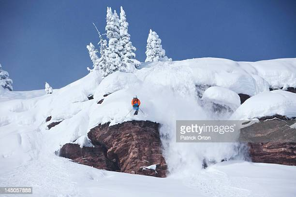 A athletic skier jumping off a cliff in the backcountry on a sunny powder day in Colorado.