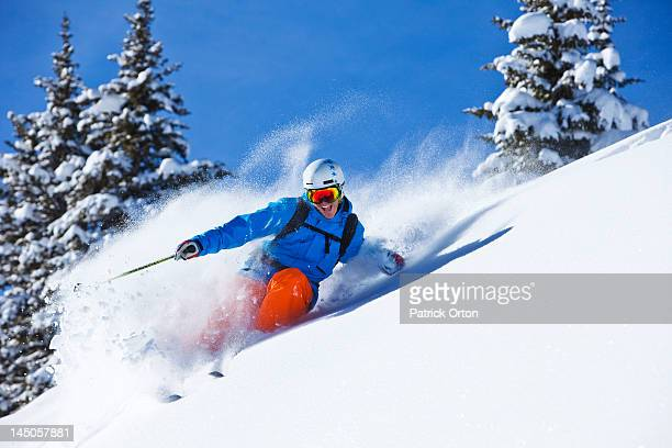 a athletic skier smiling rips fresh powder turns in the backcountry on a sunny day in colorado. - powder snow stock pictures, royalty-free photos & images