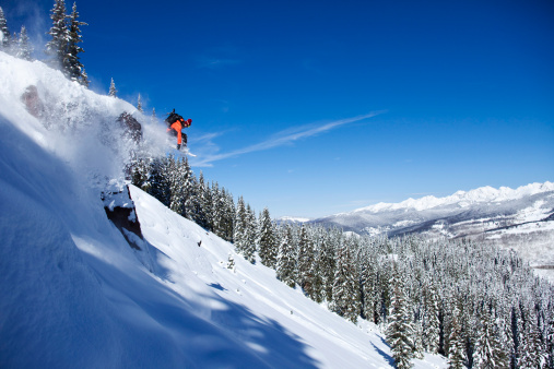 A athletic snowboarder jumping off a cliff on a sunny powder day in Colorado. - gettyimageskorea