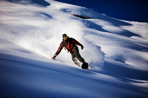 A athletic snowboarder rips fresh powder turns in the backcountry on a sunny day in Colorado. - gettyimageskorea