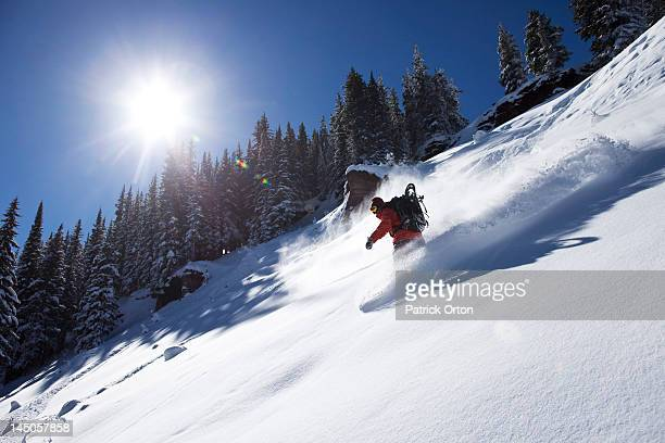 A athletic snowboarder rips fresh powder turns on a sunny day in Colorado.