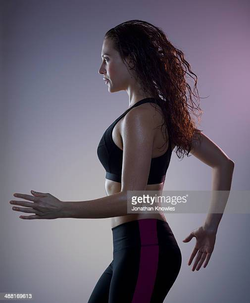 athletic, sweaty female running, side view - forward athlete stock pictures, royalty-free photos & images