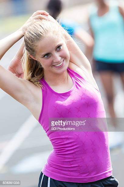 Athletic teen student stretching before race at track event