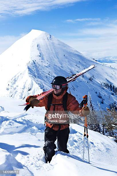 a athletic telemark skier looks out while hiking on the top a mountain in montana. - bozeman stock pictures, royalty-free photos & images