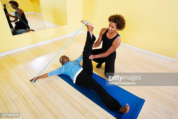 Athletic trainer helping woman with exercise