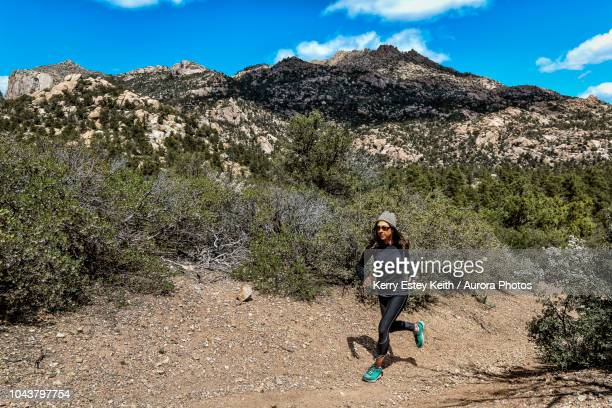 athletic ultra marathon woman running in mountains - kerry estey keith stock photos and pictures