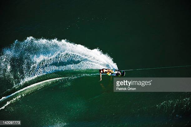 a athletic wakeboarder carves and slashes on a calm day in idaho. shot from above. - waterskiing stock photos and pictures