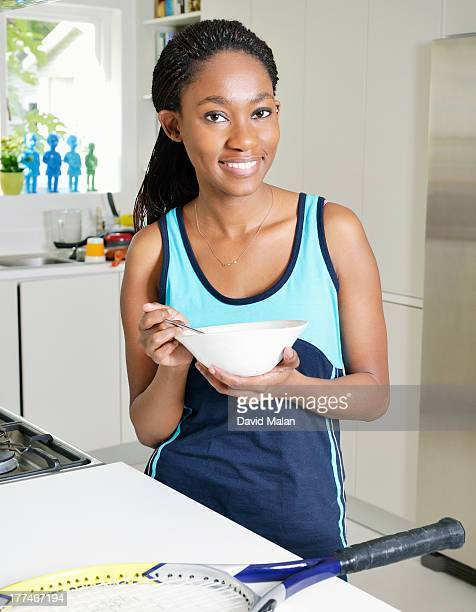 Athletic woman at home eating from a bowl