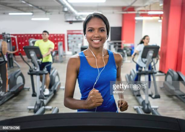 Athletic woman at the gym running on the treadmill