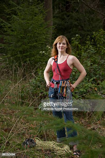 Athletic woman climbing gear standing in a forest.