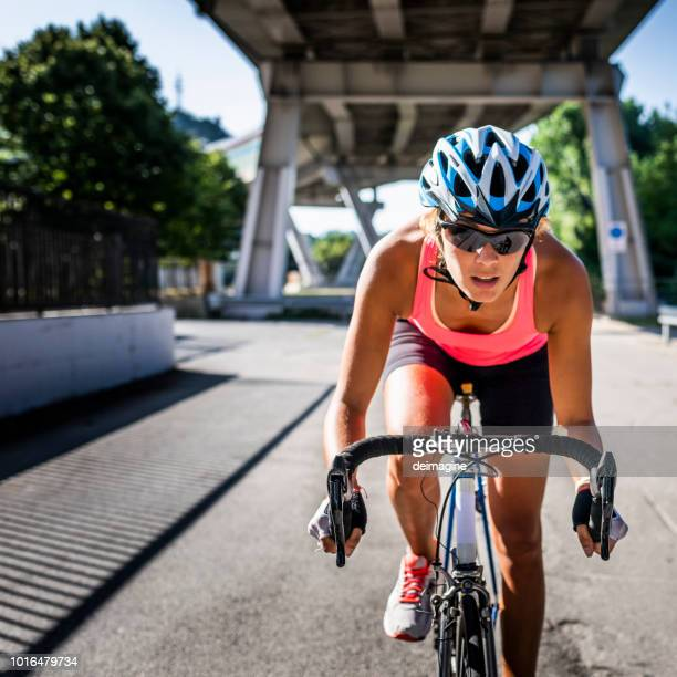 athletic woman cycling road bicycle in the city - cycling helmet stock pictures, royalty-free photos & images