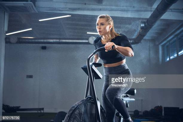 athletic woman doing airbike workout at gym - peloton stock pictures, royalty-free photos & images