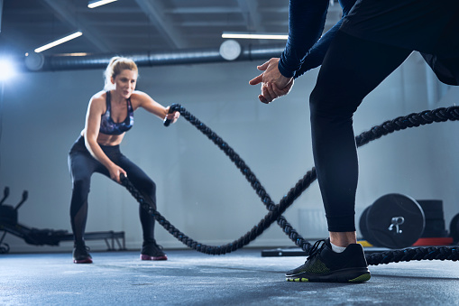 Athletic woman doing battlerope exercise with personal trainer at gym - gettyimageskorea