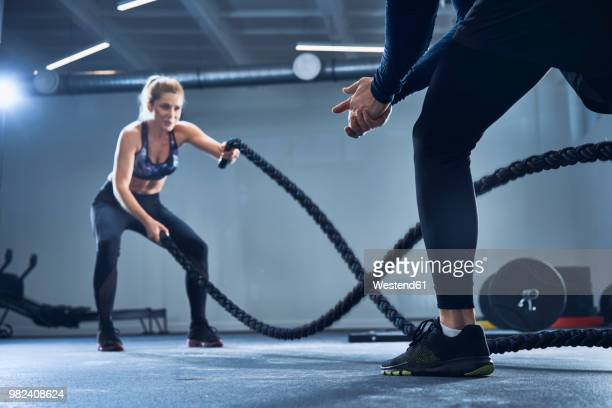 athletic woman doing battlerope exercise with personal trainer at gym - entrenador fotografías e imágenes de stock