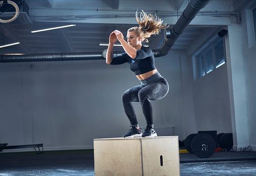 Athletic woman doing box jump exercise at gym - gettyimageskorea