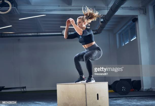 athletic woman doing box jump exercise at gym - strength training stock pictures, royalty-free photos & images