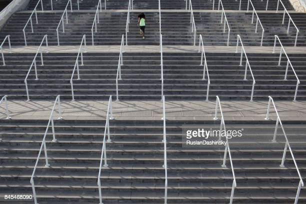 Athletic woman doing exercises, running upstairs on stadium stairs.