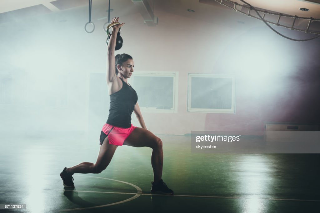 Athletic woman doing lunges with kettle bell in a gym. : Stock Photo