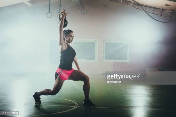 athletic woman doing lunges with kettle bell in a gym. - circuit training stock photos and pictures