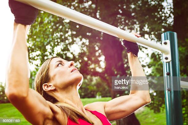 Athletic Woman Doing Pull-Ups On a Sunny Day