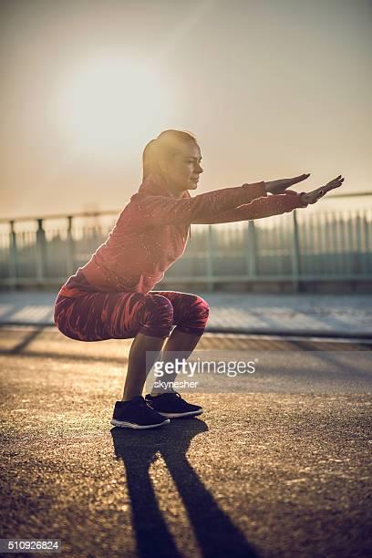 Femme athlétique faire des squats sur une route au coucher de soleil.