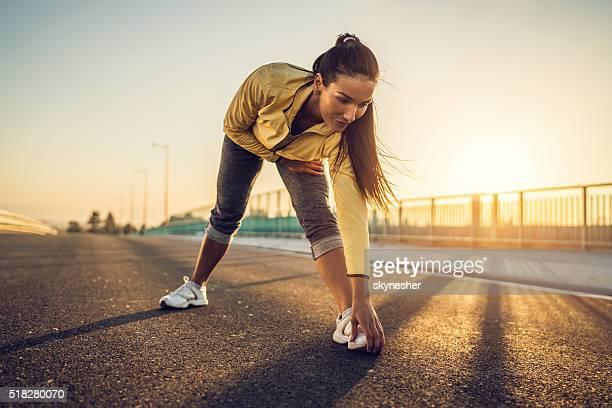 Sportive Femme faisant des étirements exercice au coucher de soleil.
