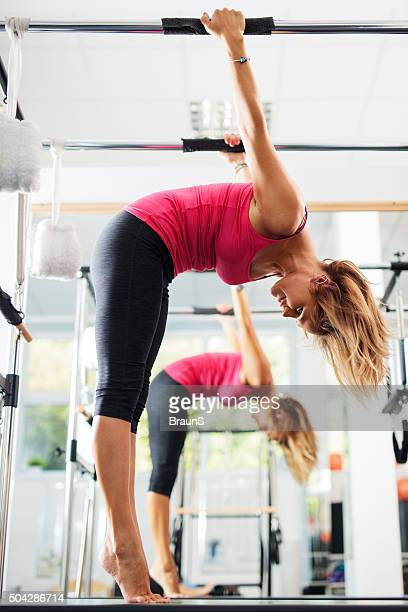 Athletic woman doing stretching exercises on Pilates machine.