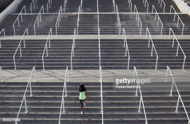 Athletic woman doing upstairs running exercise on stadium porch.