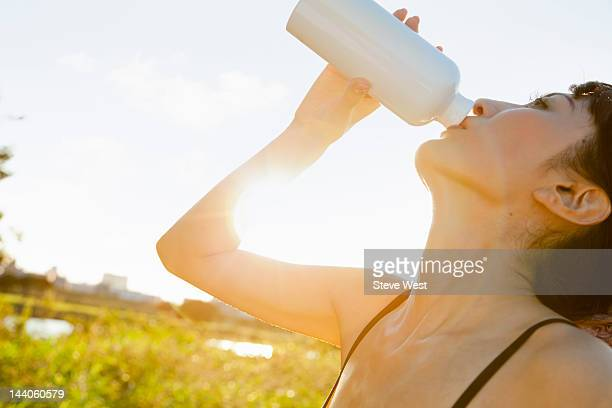 Athletic woman drinking from water bottle