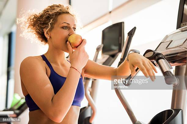 Athletische Frau, die Apfel isst und ein Fitnessraum.