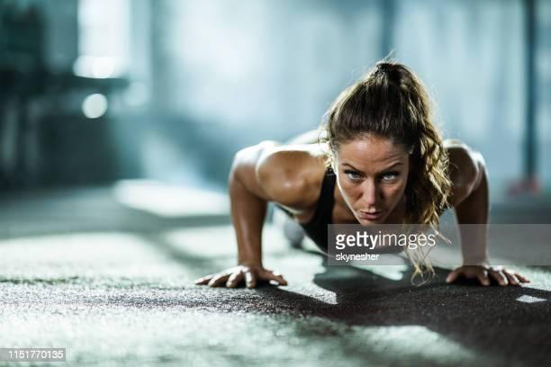 athletikerin übt push-ups in einem gesundheitsclub aus. - fitnesstraining stock-fotos und bilder