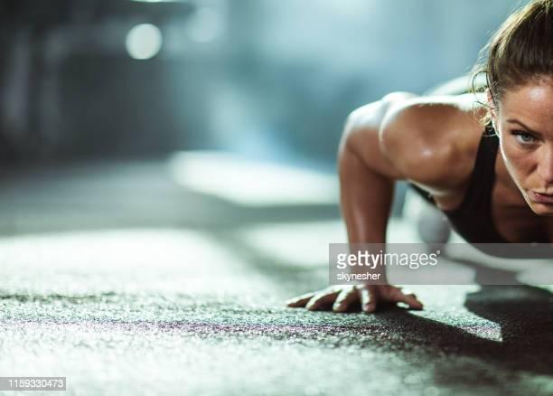 atletische vrouw de uitoefening van push-ups in een health club. - gespierd stockfoto's en -beelden
