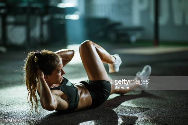 athletic woman exercising sit-ups in a health club. - athleticism stock pictures, royalty-free photos & images