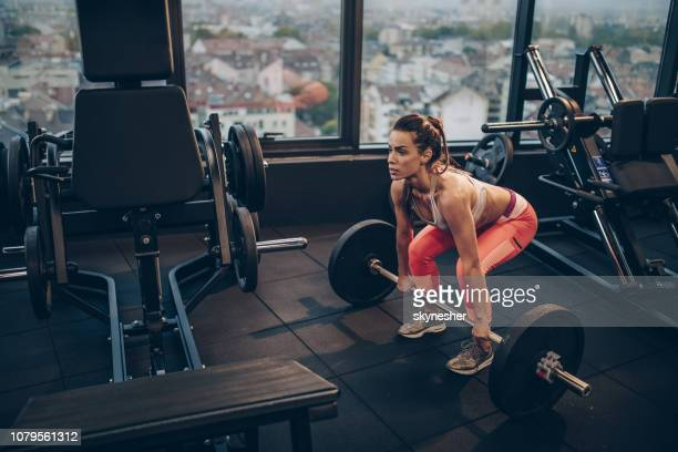 Athletic woman exercising with barbell in a health club.